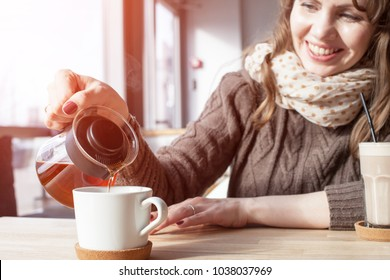 woman pours tea from a teapot in a cafe