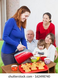 Woman pours tea from teapot for three generations family