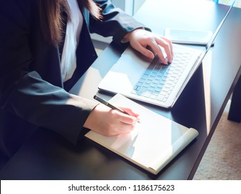 woman power and industry 4.0 concept from beauty asian business woman hand in black suit use her modern laptop check database and record in blank paper