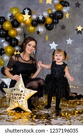 Woman power party with beautiful model mother and cute baby daughter dressed in airy black dresses celebrating love with golden stars and air baloons. Pillow stars SUPER STAR designed by photographer