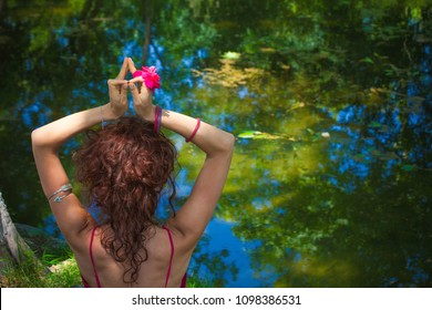 woman practice yoga meditation in front lake hands in mudra gesture with flower in hand back view summer day