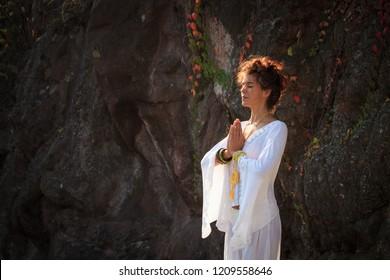 woman practice yoga outdoor autumn day hands in mudra namaste gesture