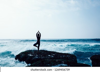 Woman practice yoga at the seaside coral cliff edge