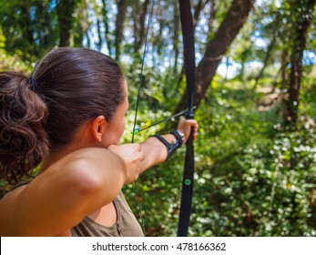 Woman practices archery in the forest with bow and arrow