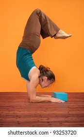 Woman practices Pincha Mayurasana over orange background