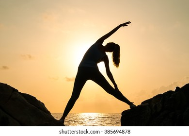 The woman practices yoga at dawn, there is an asana on a stone, dawn and an image of the girl, to enjoy dawn, to be happy with life, a beautiful body, ideal yoga,The girl meditates