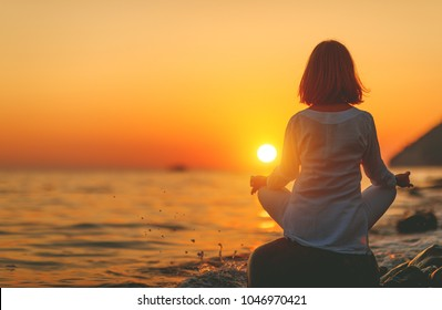 woman practices yoga and meditates in the lotus position on sunset beach