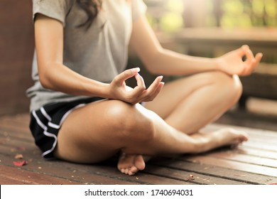 Woman practices yoga and meditates in the lotus position in peaceful place