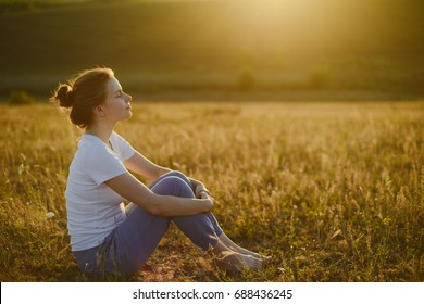 woman practices yoga and meditates in the lotus position on the nature.  Girl Meditate at the Mountains. Woman meditating in the lotus position closeup