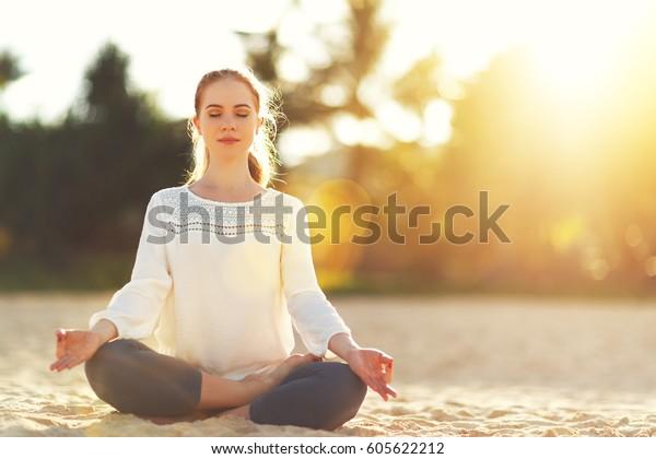 las mujeres practican yoga y medita en la posición del loto en la playa