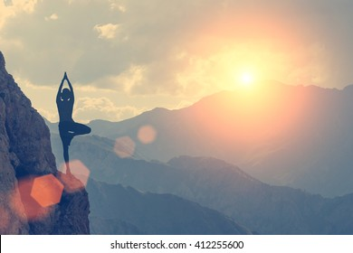 A woman practices yoga on a background of mountains and sky. Toned
