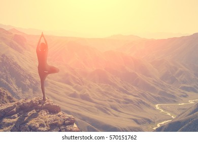 A woman practices yoga on a background of mountains and sky
