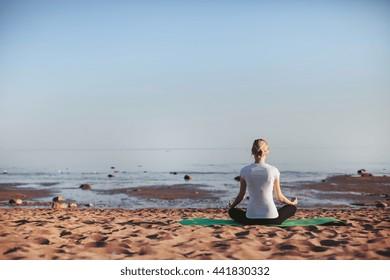 woman practices yoga on the beach