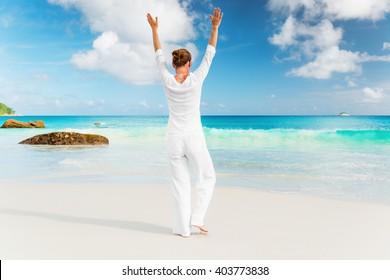 Woman practices yoga on the tropical beach