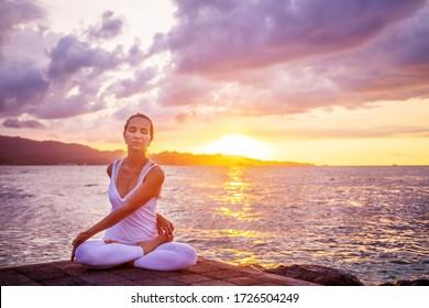 Woman practices yoga at seashore