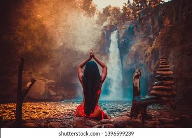 Woman practices yoga at Sekumpul waterfall on Bali in indonesia