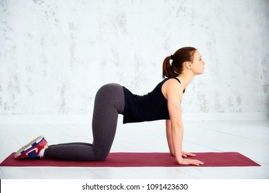 Woman practicing advanced yoga. Cow, Bitilasana, asana paired with Cat Pose on the exhale. Full length