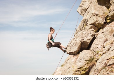 a woman practicing climbing on a mountain of rocks