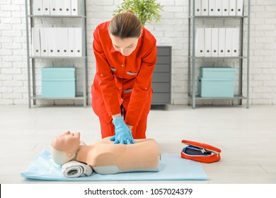 Woman practicing CPR on mannequin at first aid class