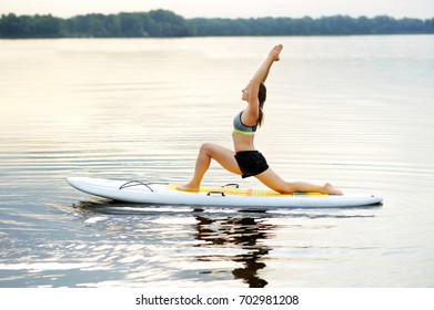 Woman practicing Crescent Lunge yoga Pose on the paddle board in the morning