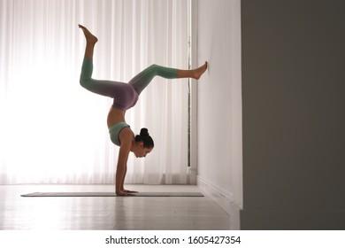 Woman practicing downward facing tree asana in yoga studio. Adho mukha vrksasana pose