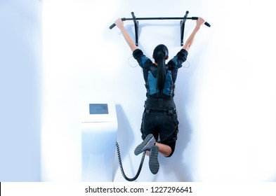 Woman practicing EMS training , doing pull ups