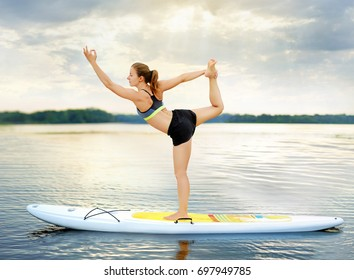 Woman practicing Lord of the Dance  yoga Pose balancing on paddle board