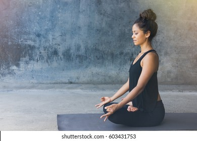 Woman practicing meditation in a urban background