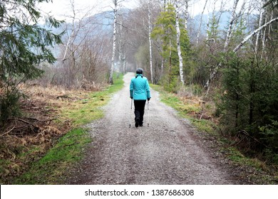 Woman is practicing Nordic Walking on a lonley path trough the forest, Allgäu, Bavaria