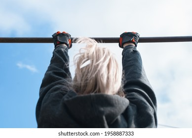 Woman practicing pull-ups on the bar outside. Outdoor workout. Active lifestyle. Back view, focus on hands