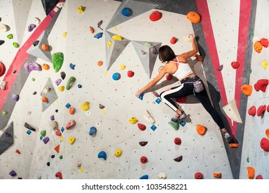 Woman practicing rock climbing on artificial wall indoors. Active lifestyle and bouldering concept.