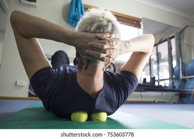 A woman practicing self-massage technique with tennis ball