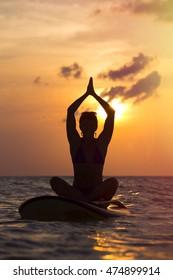 Woman practicing SUP yoga at sunset, meditating on a paddleboard.