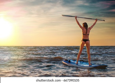 Woman practicing SUP yoga at sunset, meditating on a paddle board on sunset.