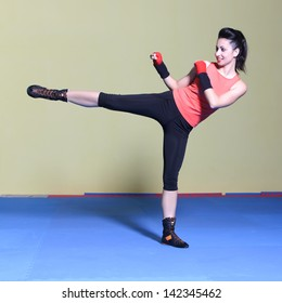 Woman practicing tae- bo exercises, kicking forward with legs in the gym