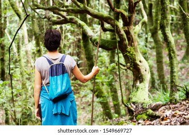 woman practicing trekking hiking in forest, Madeira island routes