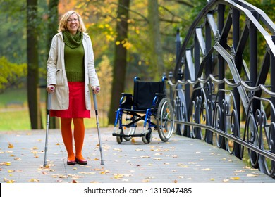 woman practicing walking on crutches in green park and wheelchair standing in the background
