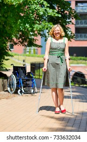 woman practicing walking on crutches in the park with wheelchair standing in the background