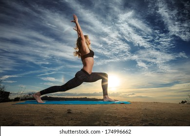 Woman practicing Warrior yoga pose outdoors over sunset sky background.