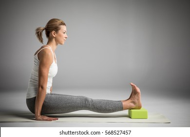 Woman practicing yoga in Angusthasana handstand pose with yoga block isolated on grey