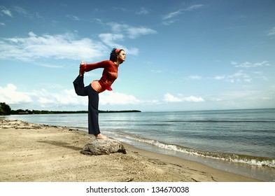 Woman practicing a yoga balance by the sea