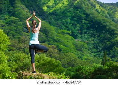 Woman practicing yoga in a beautiful outdoor setting. Meditation and body balance concept.