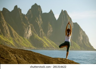 woman is practicing yoga between mountains in Norway