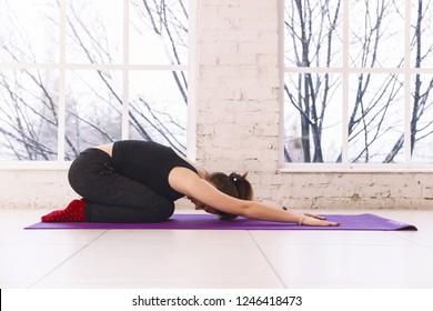 woman practicing yoga, doing child pose Balasana on the floor of light room on yoga mat indoors.