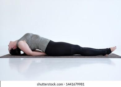 Woman practicing yoga, doing Matsyasana exercise, Fish pose for beginner. Indoor full length in white studio
