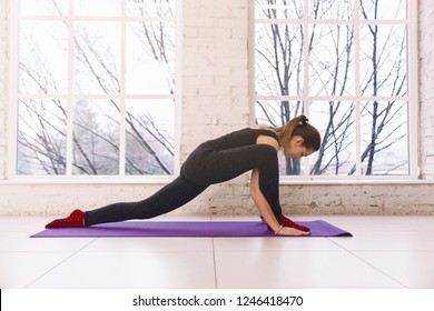 Woman practicing yoga, doing stratching  legs yoga pose on the floor of light room on yoga mat indoors. Warm up, workout