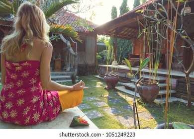 Woman practicing yoga and holding canang sari - offering for Gods. Balinese tradition.