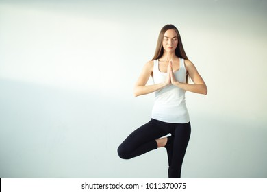woman practicing yoga, holding palms together in namaste mudra, relaxed and peaceful.