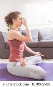 Woman Practicing Yoga at Home, breathing exercise, pranayama pose, healthy lifestyle