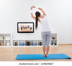 Woman practicing yoga at home standing on a mat on her living room floor while watching and participating in a class